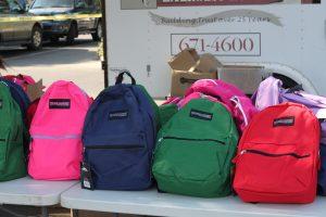 Brand new backpacks stuffed with school supplies lie waiting to surprise their new owners.